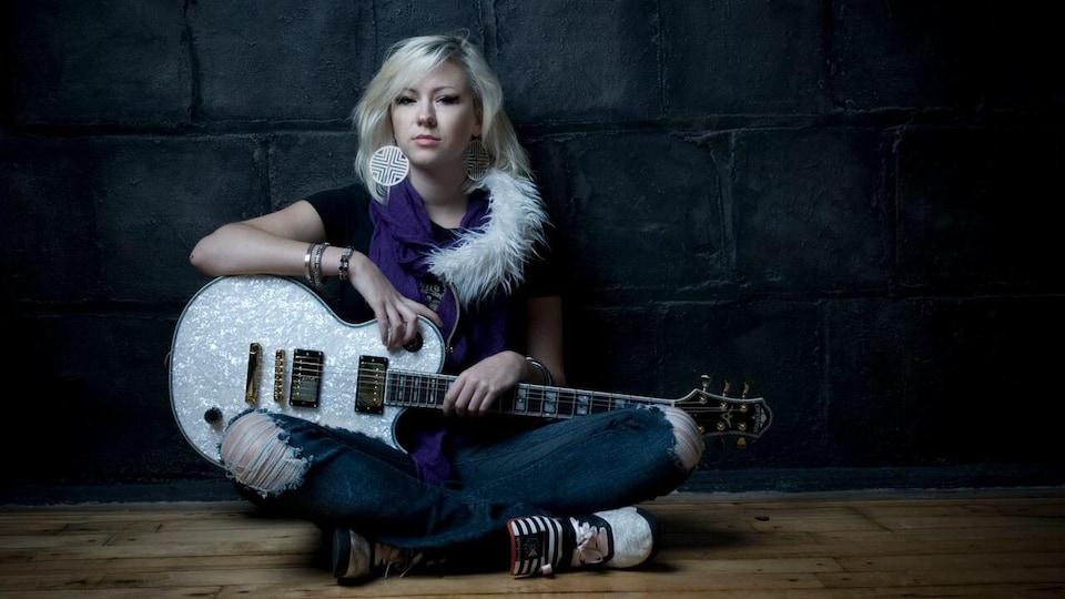 La chanteuse Val Halla avec une guitare.