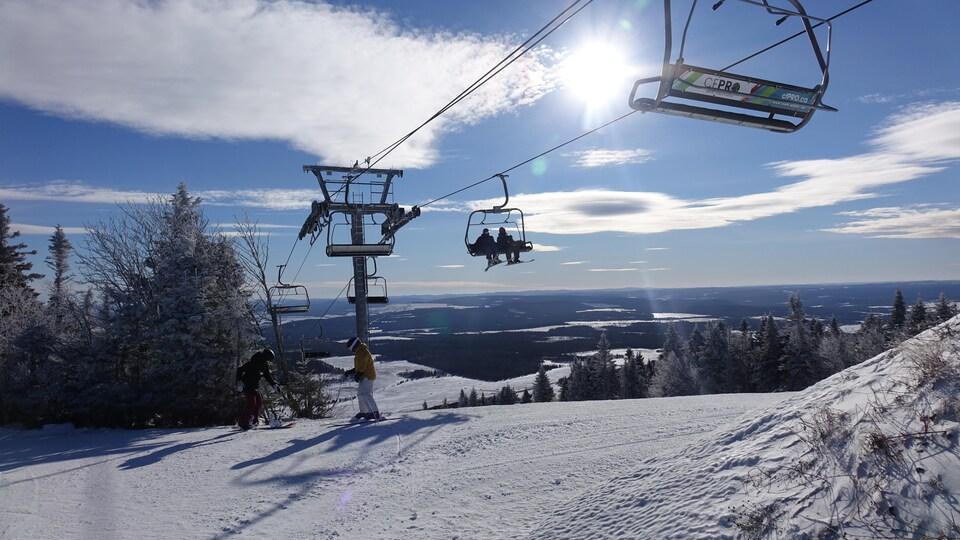 Des skieurs dans un télésiège et d'autres sur le haut d'une pente.