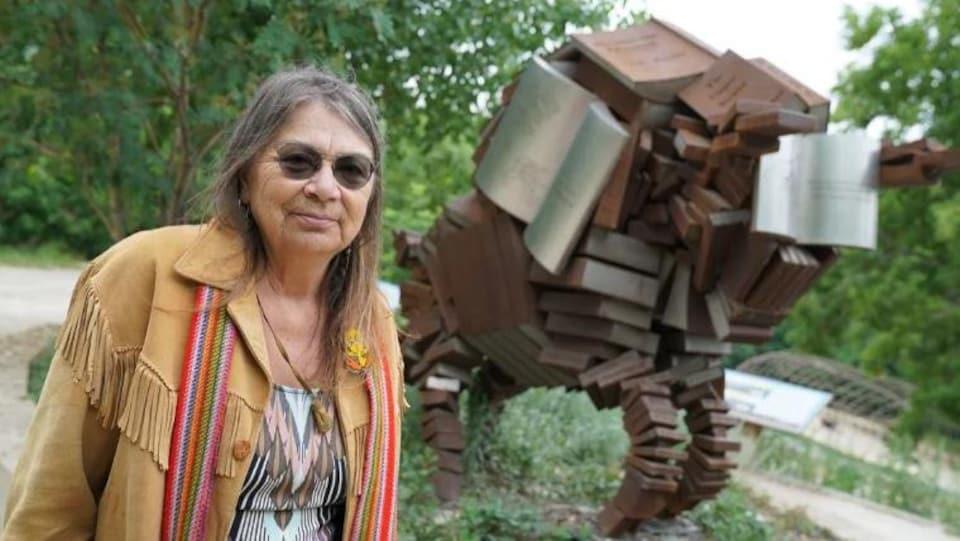 Une femme devant une statue de bison à La Fourche à Winnipeg.
