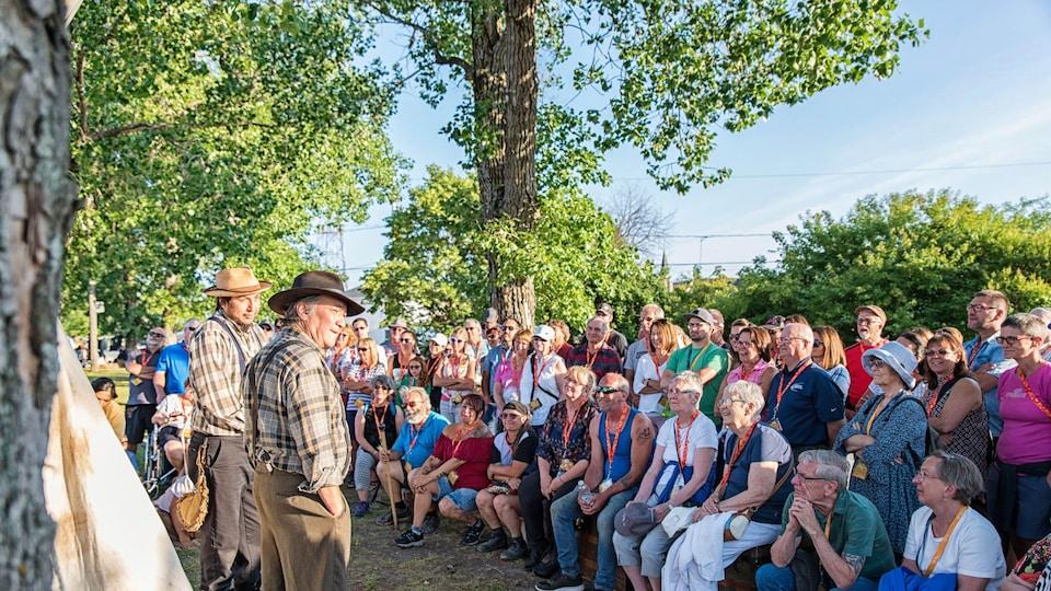 Une foule écoute deux comédiens en costume d'époque, sous les arbres.