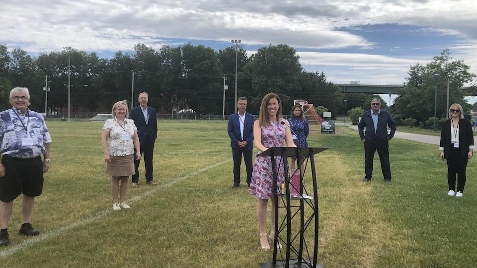 Valérie Renaud-Martin souriante devant un podium, entourée de son équipe dans un parc.