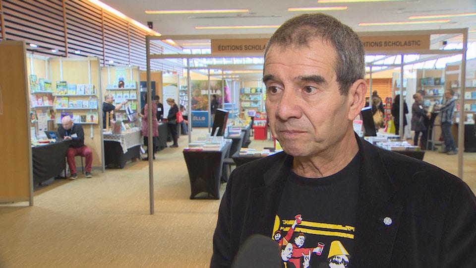 Un homme parle en entrevue dans un salon du livre.