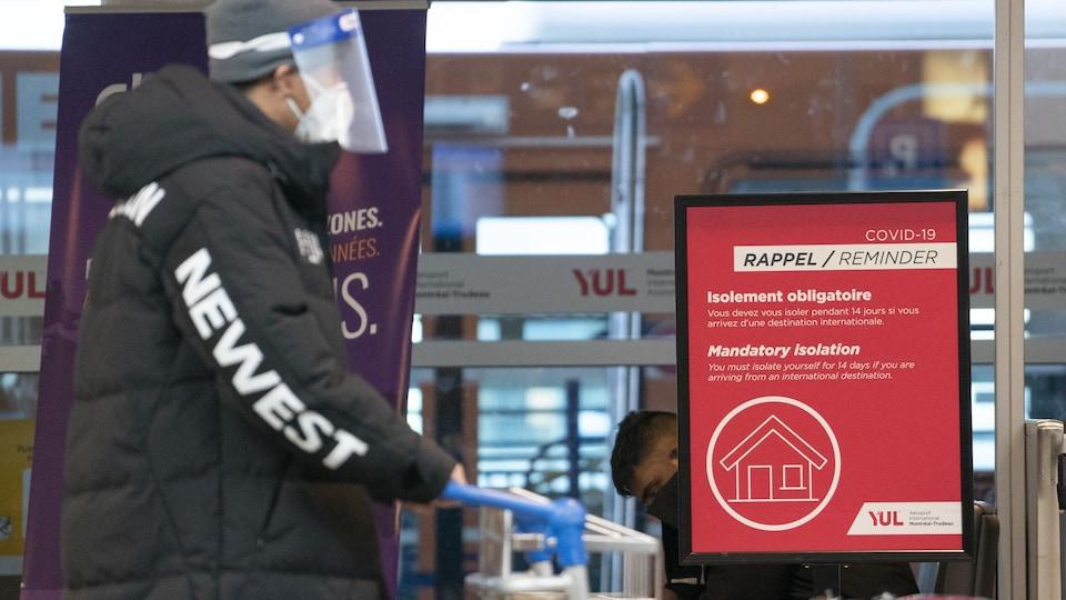Une pancarte à l'aéroport Montréal-Trudeau rappelle aux voyageurs de faire leur quarantaine.