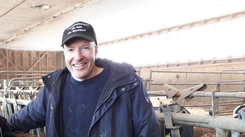 Un homme sourit à la caméra dans une étable.