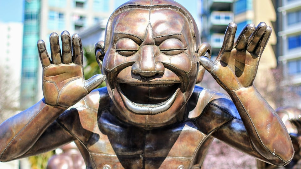 Un personnage de bronze sourit les yeux fermés.