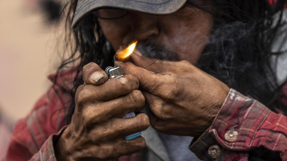 Un homme fume de la drogue dans le quartier Downtown Eastside de Vancouver.