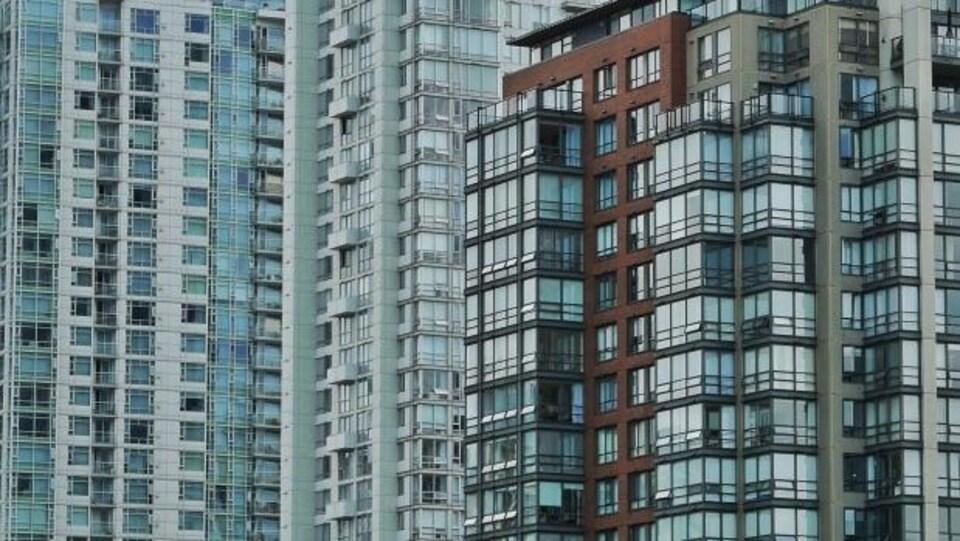 Vue sur trois tours à logement. Plan rapproché sur les fenêtres des édifices.