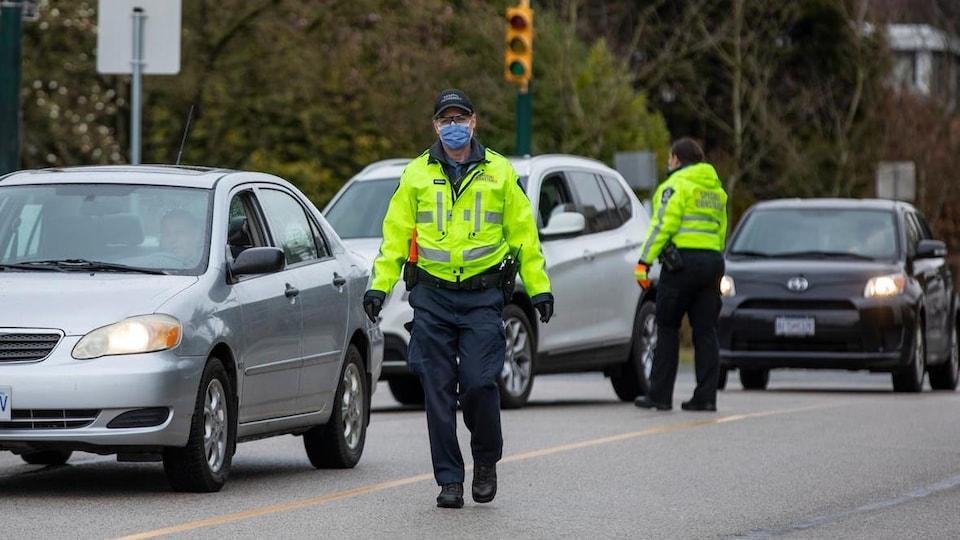 Un policer de Vancouver porte un masque et dirige la circulation.