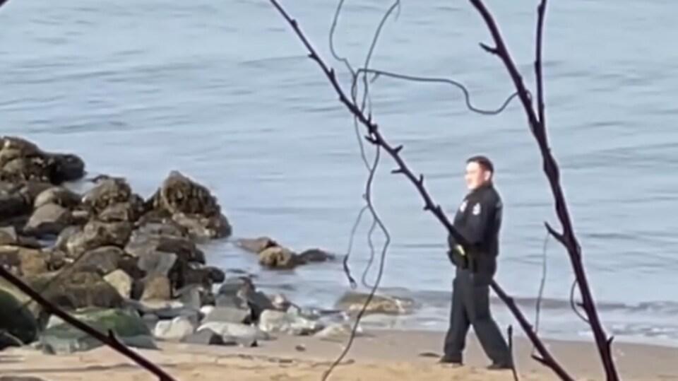 Un policier debout sur une plage.