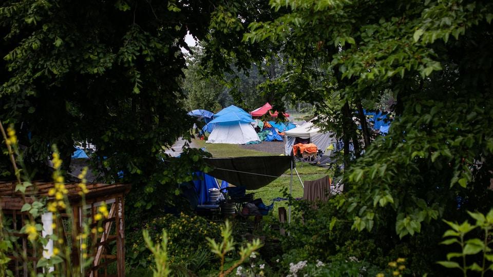 Des tentes vues à travers des arbres dans le campement du parc Strathcona, à Vancouver.