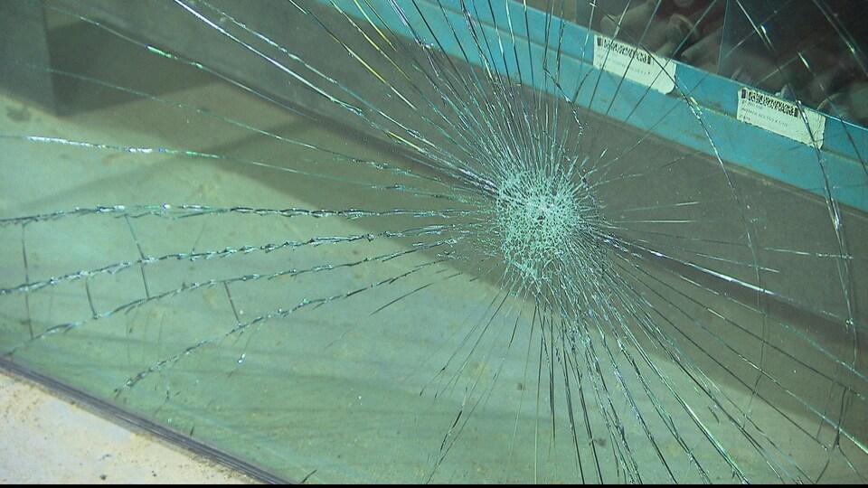 La vitre brisée a été retirée et elle est maintenant appuyée sur une étagère au moment de la prise de la photo.