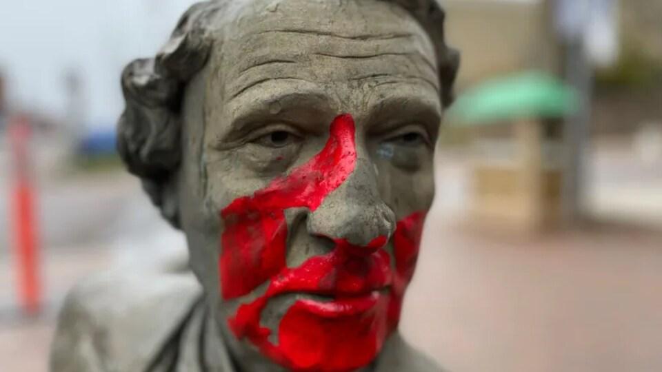 Une statue verdâtre d'un homme avec une main rouge peinte en plein milieu du visage.