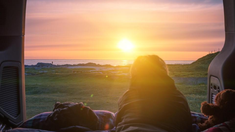 Un homme observe le coucher de soleil, allongé à l'intérieur de sa fourgonnette.