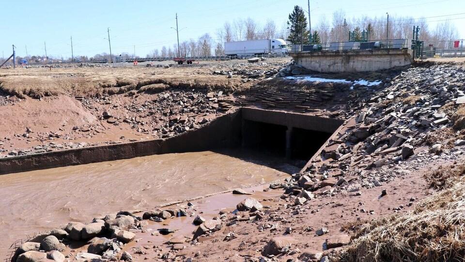 Une rivière passe sous une autoroute, il y a beaucoup de boue.