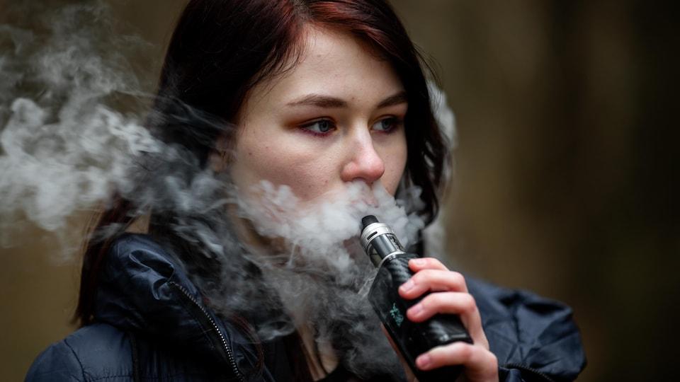 Une jeune femme fume une cigarette électronique.