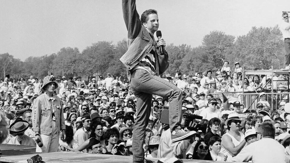 André Robitaille sur la scène devant la foule réunie sur les plaines d'Abraham à Québec.