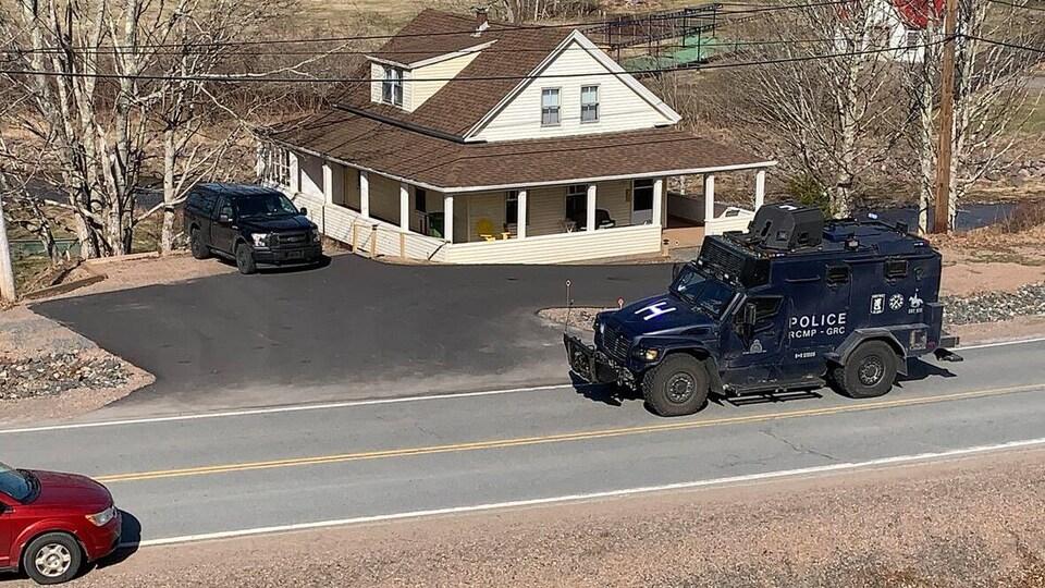 Un imposant véhicule blindé devant une maison de campagne, sur une route rurale.