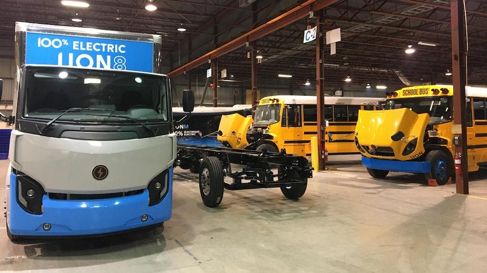 Un camion dix-roues entièrement électrique et des autobus scolaires électriques le capot ouvert dans les installations de La Compagnie électrique Lion.