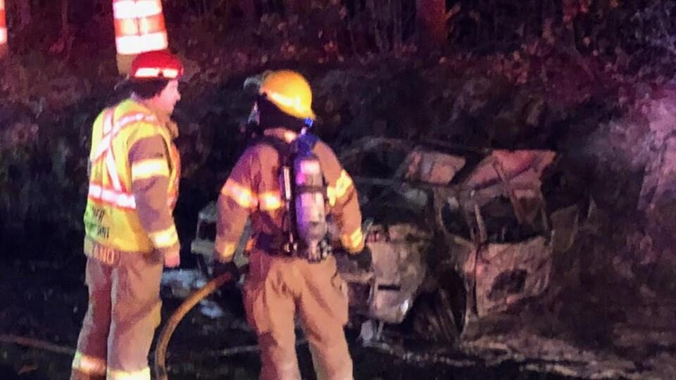 Deux pompiers devant la carcasse d'un véhicule incendié.