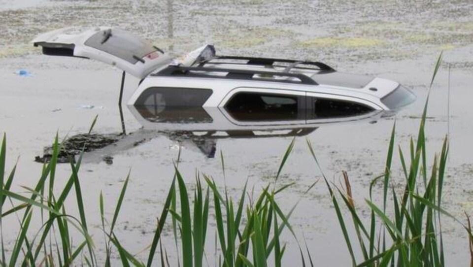 On ne voit plus que le toit ainsi que la porte du coffre arrière ouverte d'un véhicule submergé dans un marécage.