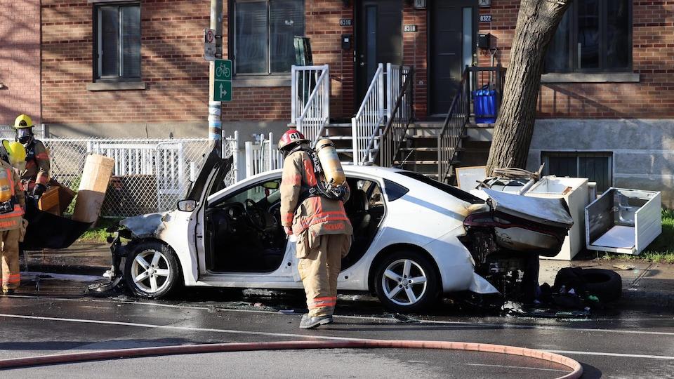 Un pompier inspecte un véhicule endommagé par le feu.