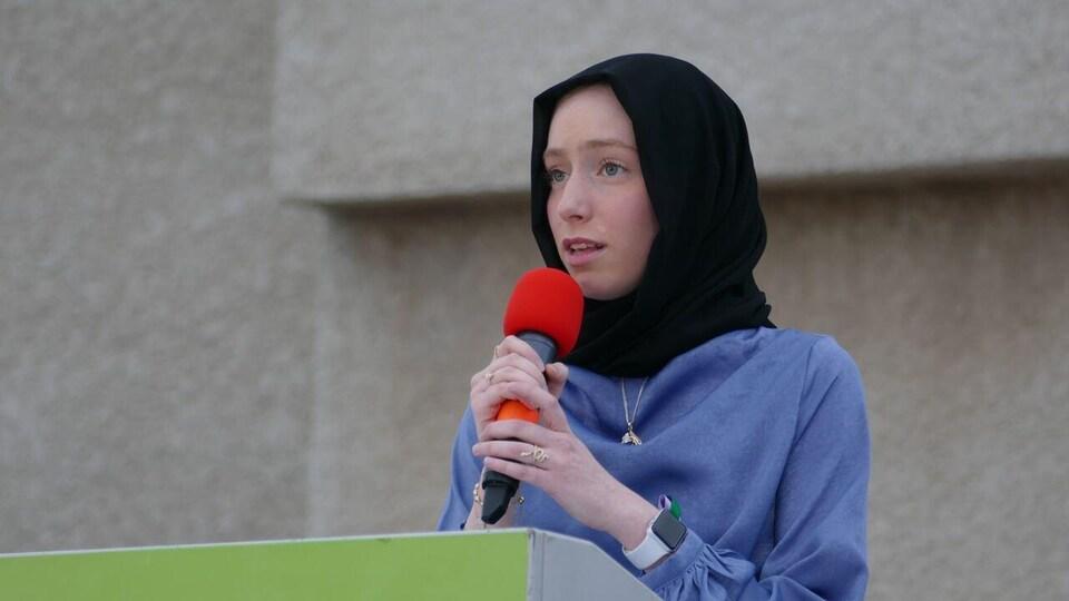 Une adolescente voilée tient un micro dans ses mains. Elle s'adresse à plusieurs personnes réunies.