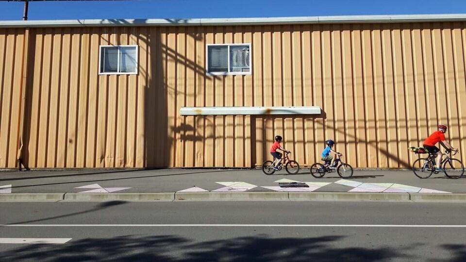 Un homme et deux enfants circulent à vélo.