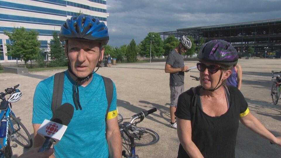 Un homme et une femme à vélo en entrevue.