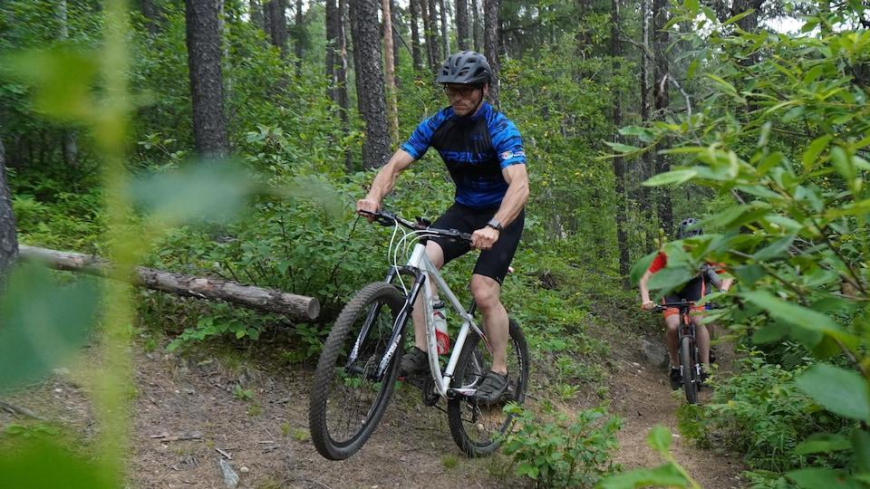 Un homme en vélo dans un sentier de vélo de montagne suivi par deux autres cyclistes.