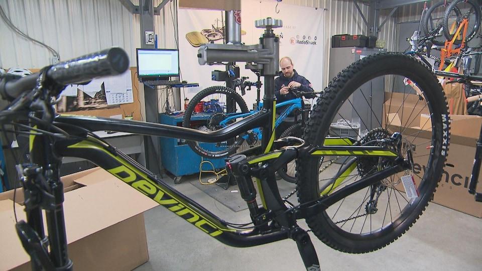 Un travailleur monte un vélo. En avant-plan, il y a un autre vélo de l'entreprise.