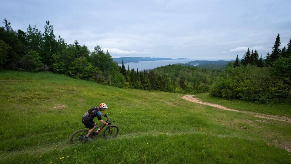 Un cycliste dévale une pente. Derrière, la baie de Gaspé.