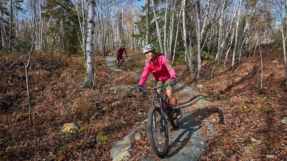 Deux cyclistes descendent une piste de vélo dans le bois.