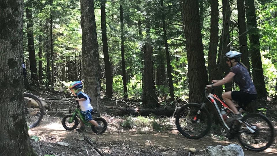 Un jeune garçon sur son vélo suivi d'une femme, aussi à vélo sur un sentier en forêt.
