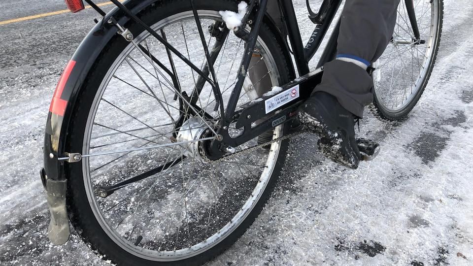 Un vélo sur une route enneigée et glacée.