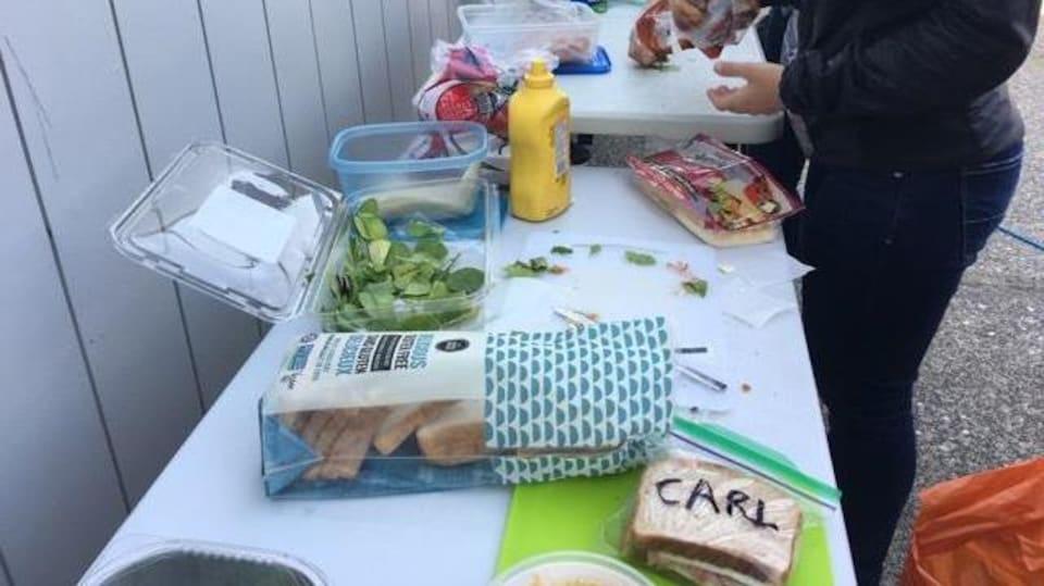 Une table de pique-nique avec de la nourriture dont un sac avec un sandwich écrit Carl au stylo marqueur.