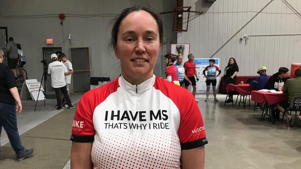 Une femme habillée en tenue de cycliste sourit dans une salle.