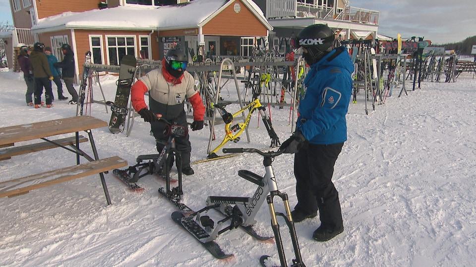 Deux personnes avec des vélo-skis dans une station de ski.
