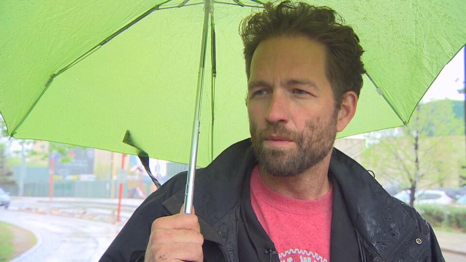 Le directeur général de Winnipeg Trails en entrevue sous un parapluie.