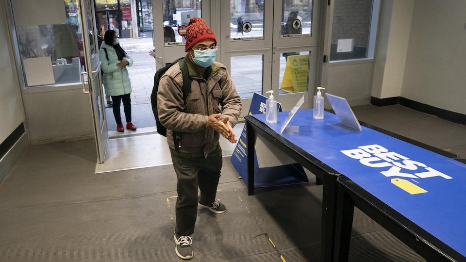 Un client se nettoie les mains en entrant dans un magasin.