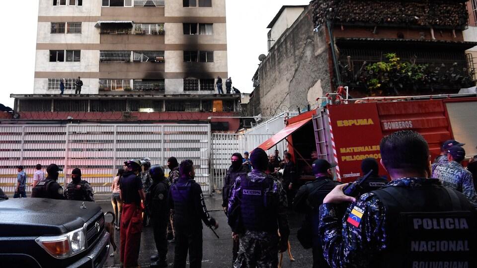Des soldats inspectent un bâtiment partiellement brûlé.