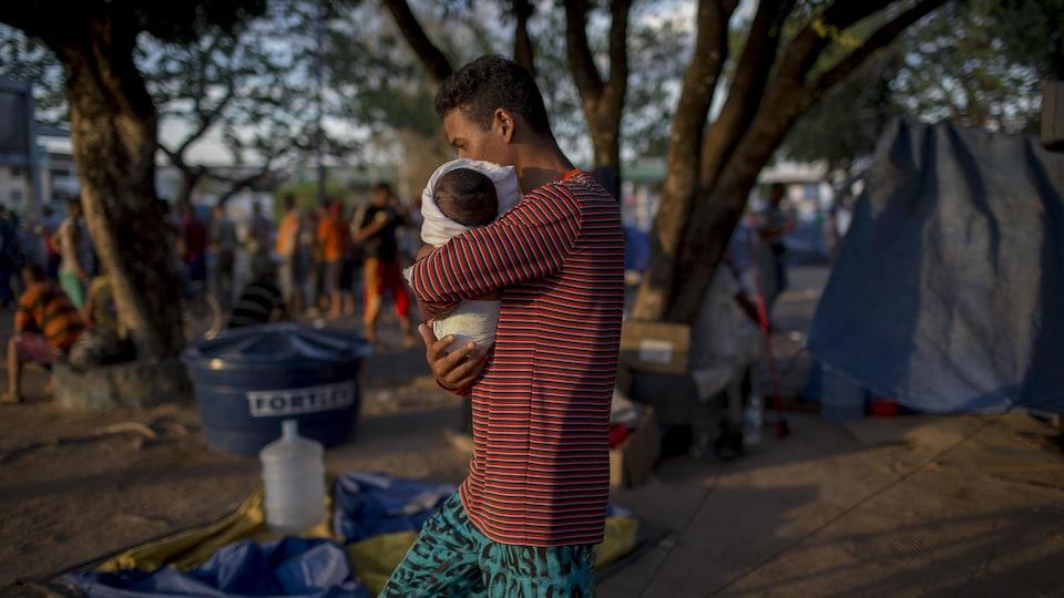 Un homme marche avec un nouveau-né dans les bras.