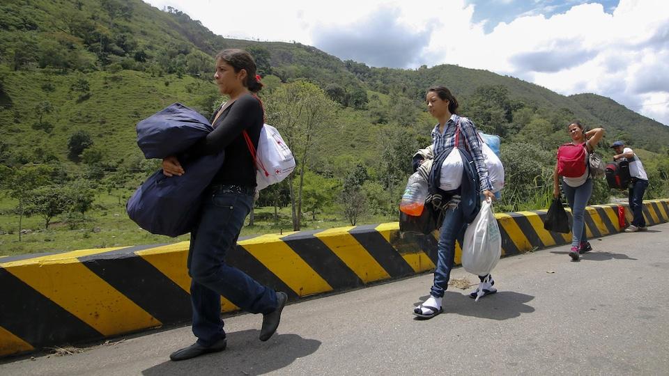Trois femmes et un homme chargés de sacs marchent sur la route.