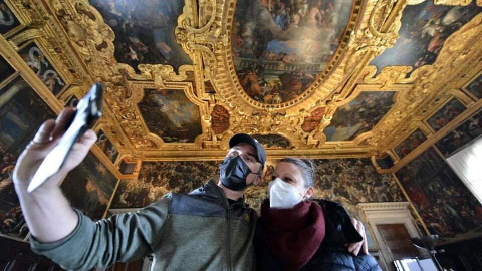 Un homme et une femme portant un masque se prennent en photo avec une téléphone cellulaire.