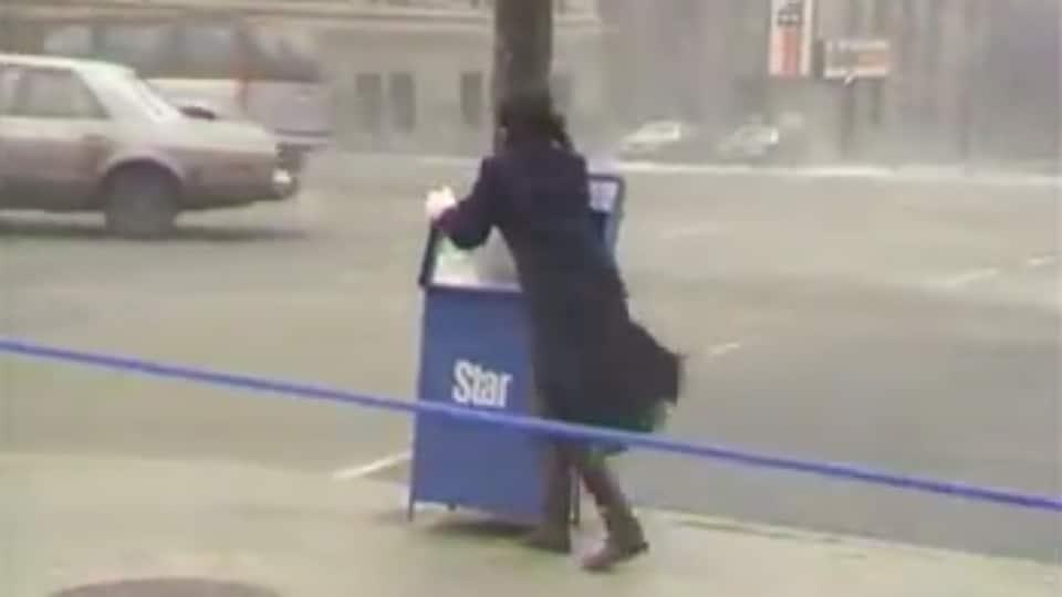 Photo d'une femme qui s'agrippe à une boîte de journaux pour ne pas être emportée par le vent.