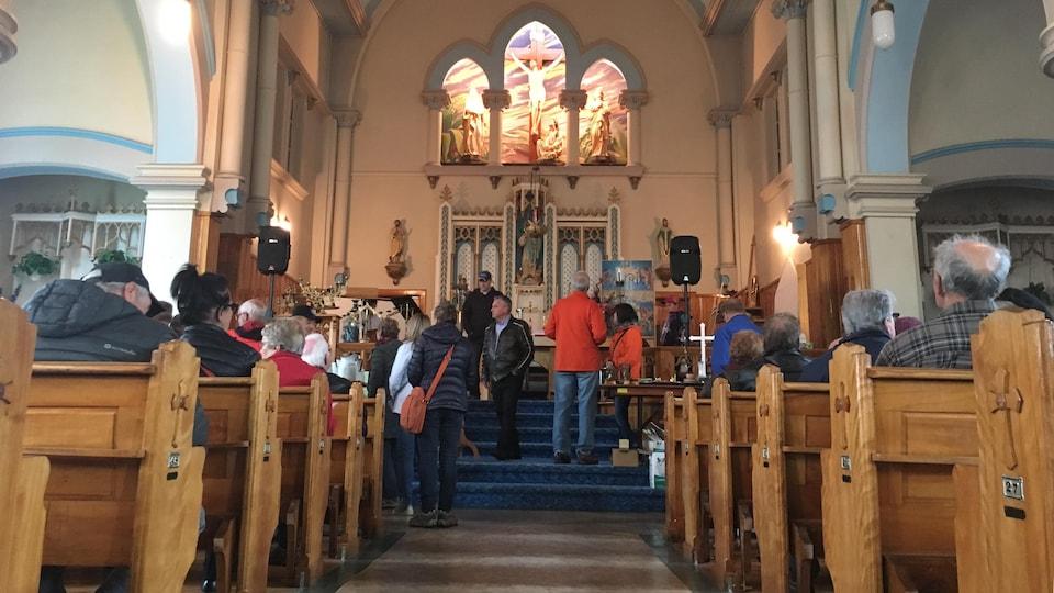 des dizaines de personnes sont assis sur les bancs dans l'église
