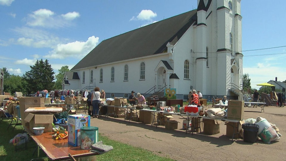 Des objets divers disposés sur des tables à l'extérieur, près d'une église.