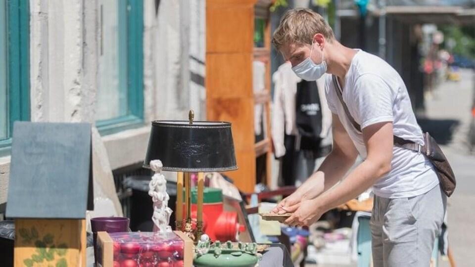 Un homme masqué se penche sur une table installée à l'extrieur et sur laqelle sont disposés beaucoup d'objets de décoration et anciens. Il tient une assiette dans ses mains et la regarde.