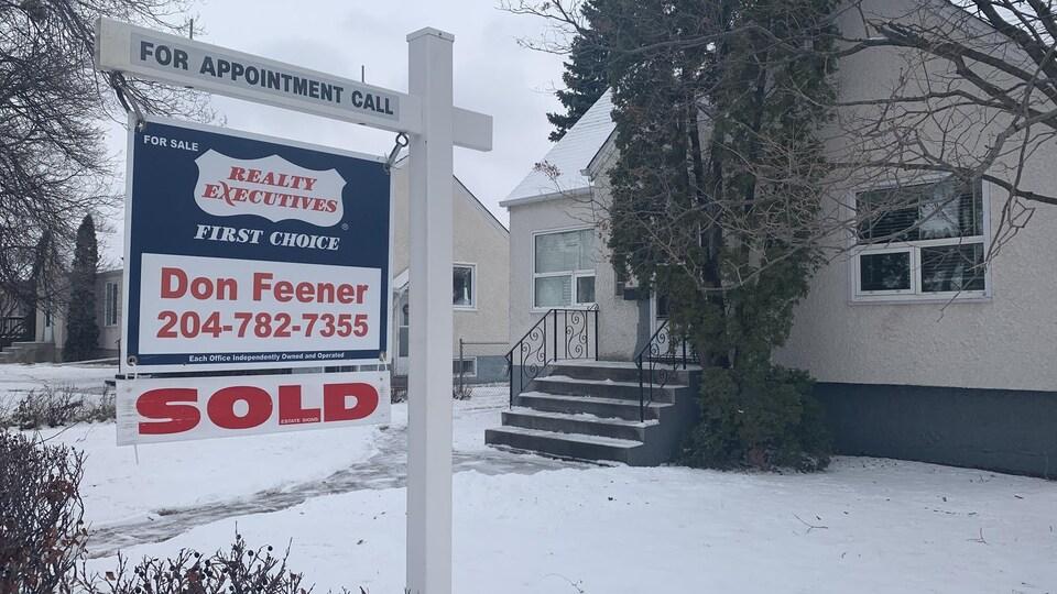 """Une affiche """"À vendre"""" devant une maison, sur laquelle est apposé le mot """"vendu"""" en anglais."""