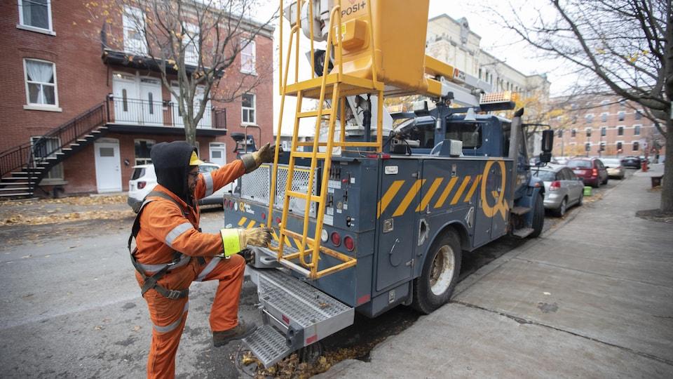 Un employé d'Hydro-Québec grimpe dans la nacelle de son camion stationné dans une rue résidentielle de Montréal.