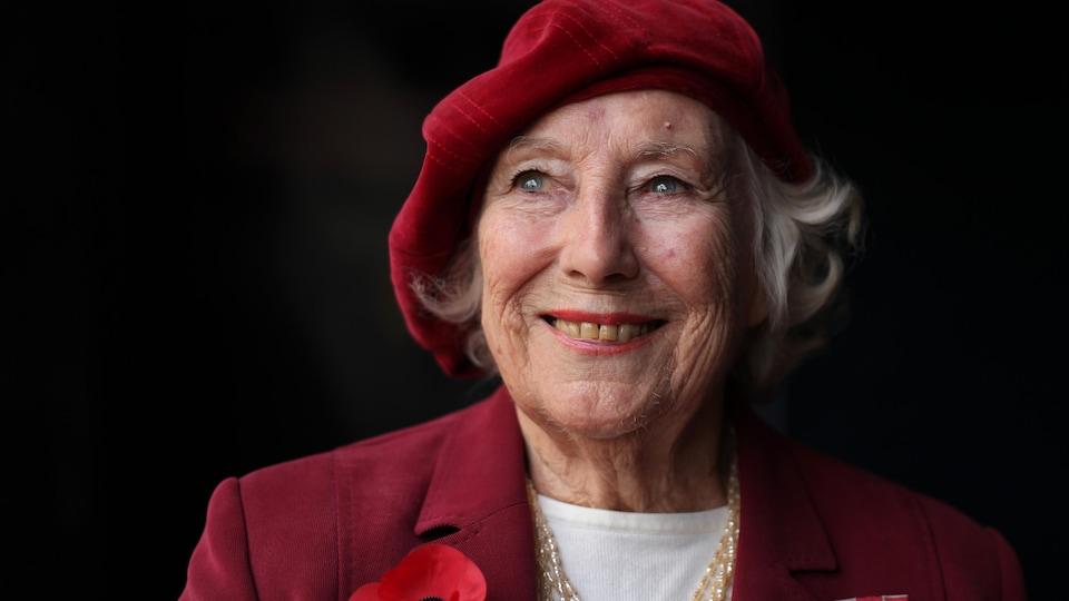 Portant un béret rouge et un veston rouge sur lequel sont attachés un coquelicot et ce qui ressemble à une insigne militaire, Dame Vera Lynn prend la pose pour la caméra.